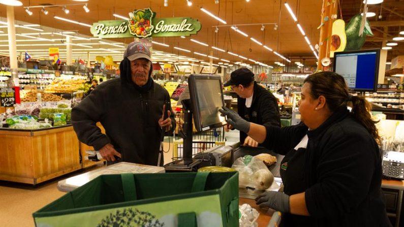 Una cajera de un supermercado atiende a un cliente en Norwalk, California. EFE/Felipe Chacón/Archivo