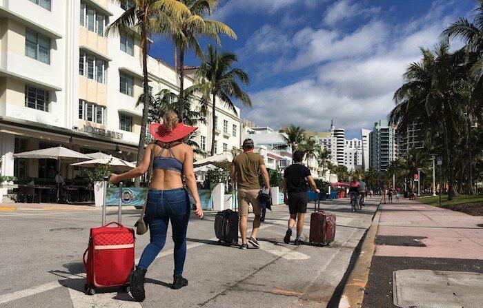 Varias personas caminan con su equipaje a través de la avenida Ocean Drive, en Miami Beach, Florida (Estados Unidos). EFE/Ivonne Malaver/Archivo