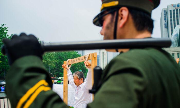 Manifestantes recrean abusos contra los derechos humanos, que tienen lugar en las cárceles chinas, en esta foto sin fecha. (Jarrod Hall/The Epoch Times)