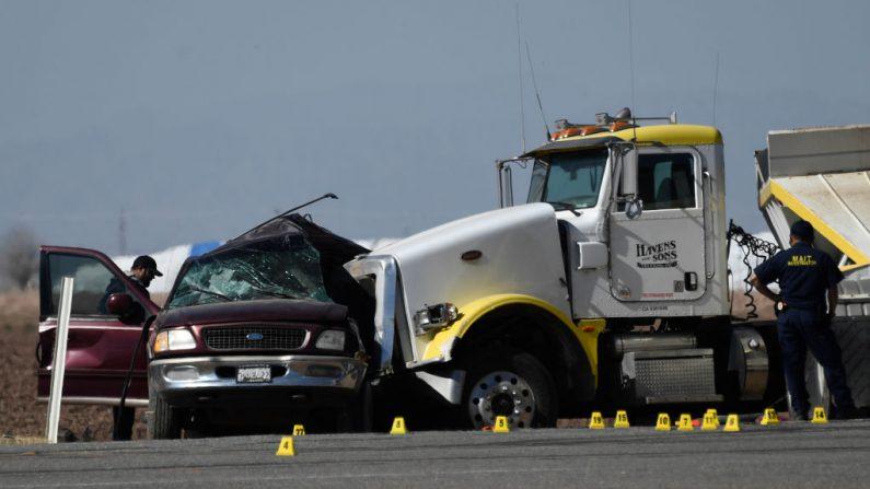 Varios investigadores examinan la escena de un accidente entre una camioneta y un camión lleno de grava cerca de Holtville, California, el 2 de marzo de 2021. (Patrick T.Fallon/AFP a través de Getty Images)