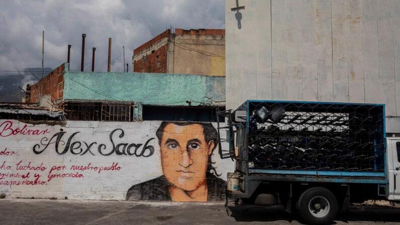 Un pequeño camión pasa junto a un grafiti con la imagen del rostro de Alex Saab el 15 de marzo de 2021, en Caracas (Venezuela). EFE/ Rayner Peña/Archivo