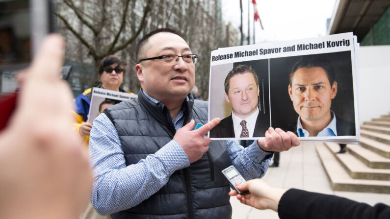 Louis Huang, de Vancouver Freedom and Democracy for China, sostiene fotos de los canadienses Michael Spavor y Michael Kovrig, detenidos por China, frente a la Corte Suprema de Columbia Británica, en Vancouver, el 6 de marzo de 2019, mientras la directora financiera de Huawei, Meng Wanzhou, comparece ante el tribunal. (Jason Redmond/AFP a través de Getty Images)
