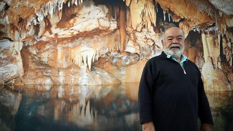 El buceador profesional francés Henri Cosquer, quien descubrió la cueva submarina de Cosquer en 1985 en las Calanques de Marsella, junto a una fotografía de la cueva de Cosquer como parte de la presentación del proyecto de réplica de la cueva de Cosquer, el 22 de noviembre de 2019 en Marsella, sur de Francia. (GERARD JULIEN / AFP)