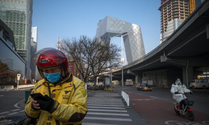 Un repartidor utiliza su teléfono en las calles del Distrito Central de Negocios en Beijing, China, el 10 de febrero de 2020. (Andrea Verdelli/Getty Images)