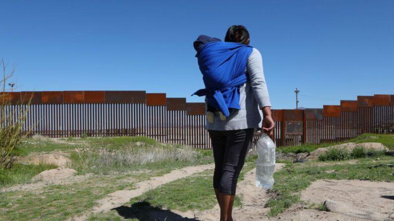 Un migrante con un niño pequeño frente al muro fronterizo que divide Sunland Park, Nuevo México, Estados Unidos, con Ciudad Juárez, estado de Chihuahua, México, el 14 de marzo de 2020. (HERIKA MARTINEZ/AFP vía Getty Images)