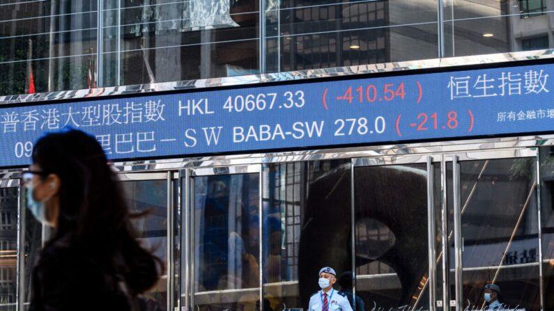 La actividad bursátil de Alibaba Group Holding Ltd (BABA-SW) (arriba C) se muestra por encima de un guardia de seguridad mientras se encuentra fuera de las torres de Exchange Square en Hong Kong el 4 de noviembre de 2020. (Anthony Walllace/AFP vía Getty Images)