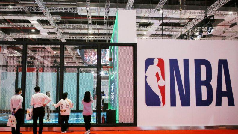 La gente junto a un logotipo de la NBA en la Exposición de la NBA en la 3a Exposición Internacional de Importaciones de China (CIIE) en Shanghai, China, el 5 de noviembre de 2020. (STR/AFP a través de Getty Images)