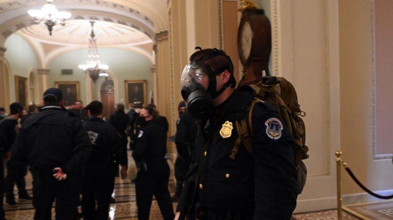 Un policía del Capitolio de EE. UU. lleva puesta una máscara de gas mientras los manifestantes irrumpen en el Capitolio, el 6 de enero de 2021, en Washington, D.C. (SAUL LOEB/AFP a través de Getty Images)
