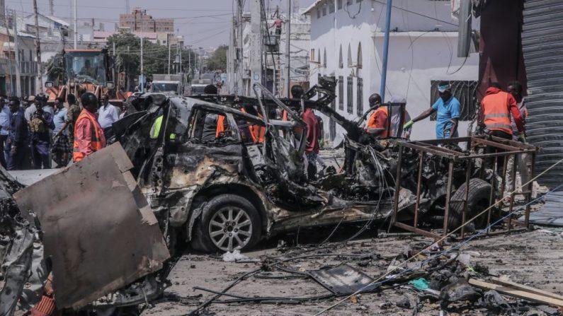 En una foto de archivo, el personal de rescate y los transeúntes se reúnen cerca de los escombros en el sitio de un atentado suicida con coche bomba cerca de un puesto de control de seguridad en Mogadiscio, Somalia, el 13 de febrero de 2021. (Abdirazak Hussein Farah / AFP vía Getty Images)
