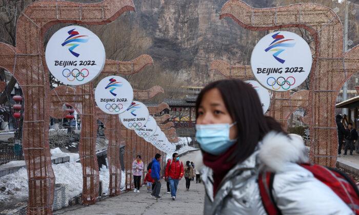 Una mujer camina delante de los logotipos de los Juegos Olímpicos de Invierno de 2022 en el Festival de Hielo de Yanqing el 26 de febrero de 2021 en Beijing, China. (Lintao Zhang/Getty Images)