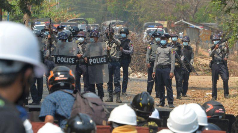 La policía antidisturbios sostiene sus armas de fuego mientras se enfrentan a los manifestantes durante una manifestación contra el golpe militar en Naypyidaw, Birmania, el 8 de marzo de 2021. (STR / AFP vía Getty Images)