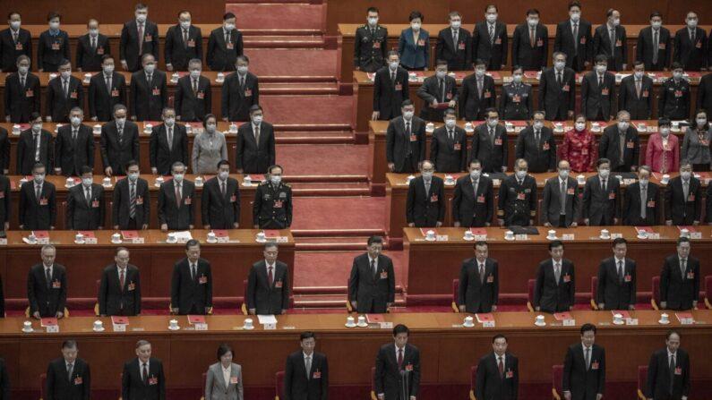 El líder chino Xi Jinping (centro) y los legisladores se ponen de pie para el himno durante la sesión de clausura de la conferencia de la legislatura títere en el Gran Salón del Pueblo en Beijing, China, el 11 de marzo de 2021. (Kevin Frayer/Getty Images)