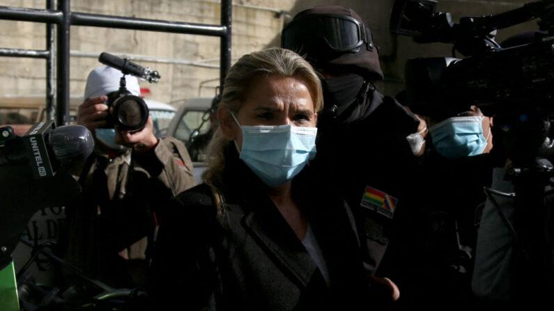 La expresidenta interina de Bolivia, Jeanine Añez, es llevada a la fiscalía por policías de la Fuerza Especial contra el Crimen (FELCC) luego de ser arrestada en La Paz, el 13 de marzo de 2021. (Luis Gandarillas / AFP a través de Getty Images)