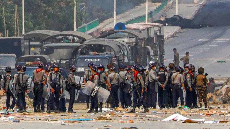 La policía se para cerca de barricadas improvisadas levantadas por manifestantes durante una represión contra las manifestaciones contra el golpe militar en el municipio de Hlaing Tharyar en Rangún, Birmania, el 14 de marzo de 2021. (STR / AFP vía Getty Images)