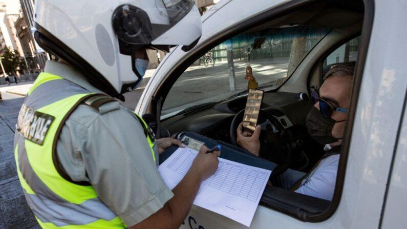 Un policía revisa el teléfono móvil de un conductor en un puesto de control en Santiago, Chile, el 27 de marzo de 2021, durante un encierro en medio de la pandemia de COVID-19. (Martin Bernetti / AFP vía Getty Images)