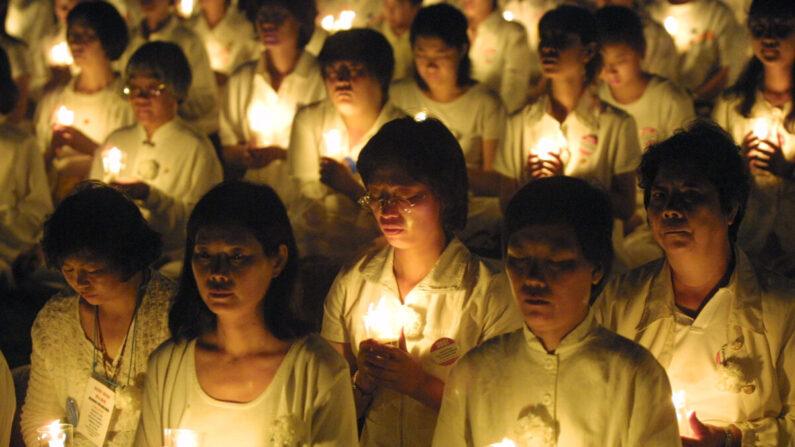 Decenas de practicantes de Falun Gong sostienen velas durante una vigilia en Washington el 19 de julio de 2001 para rendir homenaje a las vidas de aquellos en China que han sido golpeados y torturados hasta la muerte. (Alex Wong/Getty Images)