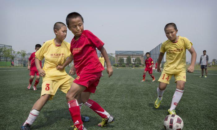 Unos niños juegan al fútbol en un cancha de entrenamiento de la Escuela Internacional de Fútbol Evergrande, en la provincia china de Guangdong. (Kevin Frayer/Getty Images)