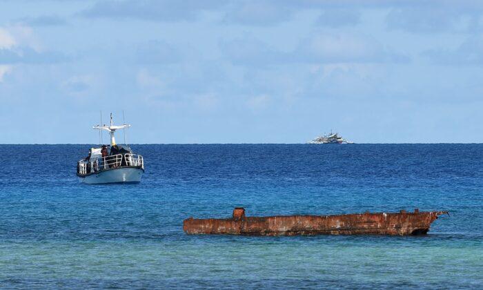 Un barco de investigación (iz) y un barco de pesca filipino (detrás a de) anclados cerca de la isla de Thitu, en las disputadas islas Spratly del Mar de China Meridional, el 21 de abril de 2017. (TED ALJIBE/AFP vía Getty Images)