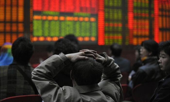 Varios inversores observan un tablero electrónico que muestra los precios de las acciones en una agencia de valores en Beijing el 20 de marzo de 2008. (Peter Parks/AFP vía Getty Images)