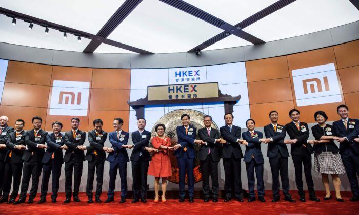 El fundador de Xiaomi, Lei Jun (en el centro, con corbata naranja), se da la mano con otros ejecutivos durante la salida a bolsa de la compañía en la HKSE en Hong Kong el 9 de julio de 2018. (Isaac Lawrence/AFP vía Getty Images)