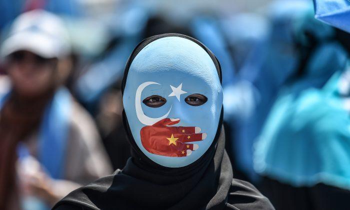 Un manifestante con una máscara pintada con los colores de la bandera del Turquestán Oriental —la que algunos uigures separatistas refieren como la región de Xinjiang— y una mano con los colores de la bandera china, asiste a una protesta frente al consulado chino en Estambul, el 5 de julio de 2018, para denunciar el trato de China a los musulmanes de etnia uigur, (OZAN KOSE/AFP/Getty Images)