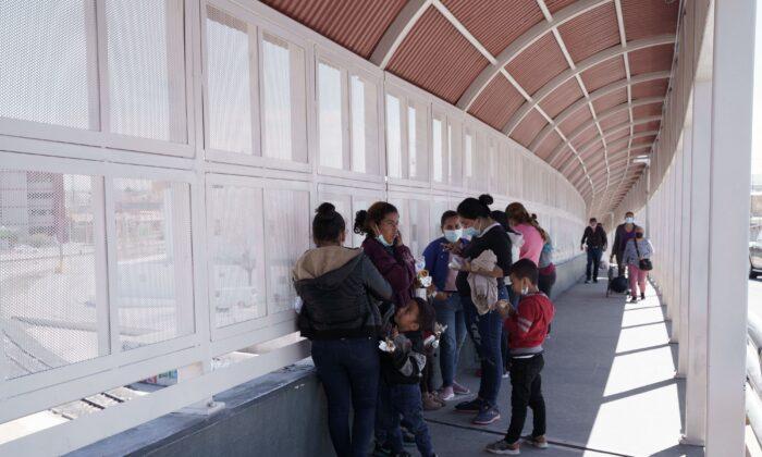 Un grupo de migrantes deportados rápidamente de Estados Unidos bajo el Título 42 esperan en el lado mexicano del puente internacional Paso del Norte entre El Paso, Texas, y Ciudad Juárez, México, el 10 de marzo de 2021. (Paul Ratje/AFP vía Getty Images)