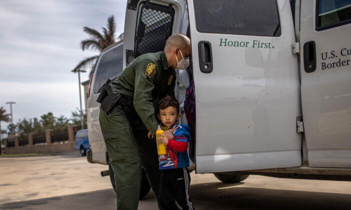 En una foto de archivo, un agente de la Patrulla Fronteriza entrega una unidad familiar que ingresó ilegalmente a Estados Unidos a una estación de autobuses en Brownsville, Texas, el 26 de febrero de 2021. (John Moore/Getty Images)