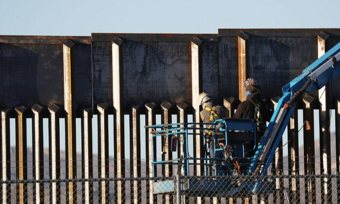 La gente trabaja en el muro fronterizo entre Estados Unidos y México en El Paso, Texas, el 12 de febrero de 2019. (Joe Raedle/Getty Images)