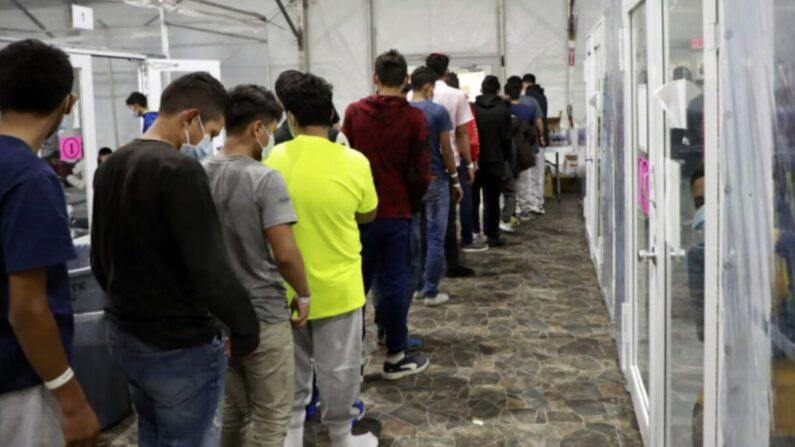 Los menores no acompañados, en su mayoría varones adolescentes, hacen fila en una instalación de procesamiento temporal en Donna, Texas, el 23 de marzo de 2021. (CBP)
