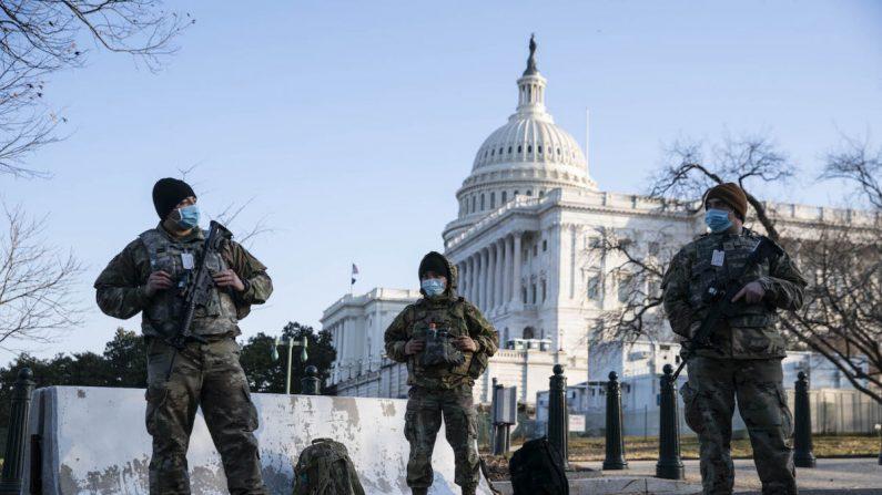 Miembros de la Guardia Nacional usan mascarillas protectoras en servicio fuera del Capitolio de los Estados Unidos en Washington, el 4 de marzo de 2021. (Sarah Silbiger/Getty Images)