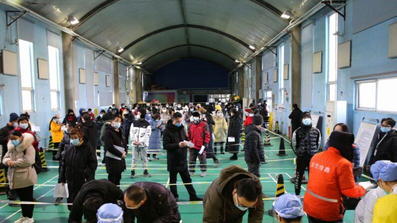 Varias personas hacen cola para recibir vacunas contra el coronavirus en un centro de vacunación temporal en Beijing el 8 de enero de 2021. (STR/CNS/AFP a través de Getty Images)