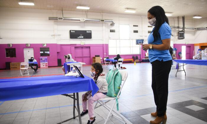 Una empleada de YMCA ayuda a una niña mientras asiste a clases por internet en un centro de aprendizaje dentro de Crenshaw Family YMCA, ya que las escuelas permanecen cerradas a la instrucción en persona en Los Ángeles, California, el 17 de febrero de 2021. (Patrick T. Fallon/AFP a través de Getty Images)