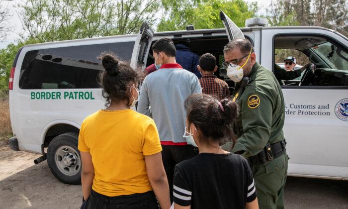 Varios menores no acompañados suben a una furgoneta de transporte de la Patrulla Fronteriza de EE. UU. después de cruzar la frontera entre EE. UU. y México en Hildalgo, Texas, el 25 de marzo de 2021. (John Moore/Getty Images)