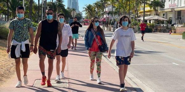 Personas con mascarillas caminan en Miami Beach, Florida (EE.UU.) el 22 de diciembre de 2020 en medio de la pandemia de Covid-19. (DANIEL SLIM / AFP a través de Getty Images)