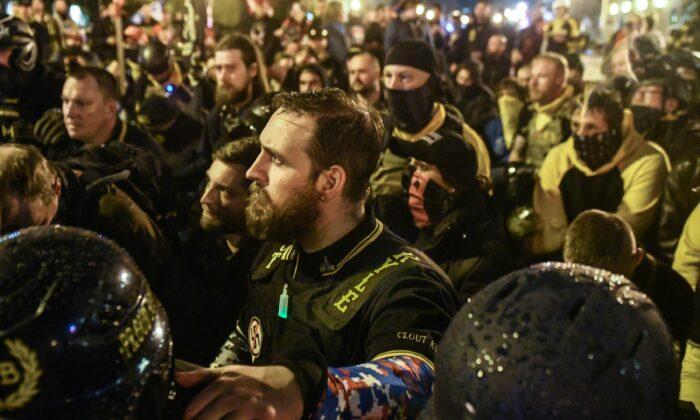 Miembros de los Proud Boys rezan por un miembro que fue apuñalado durante una protesta en Washington el 12 de diciembre de 2020. (Stephanie Keth/Getty Images)