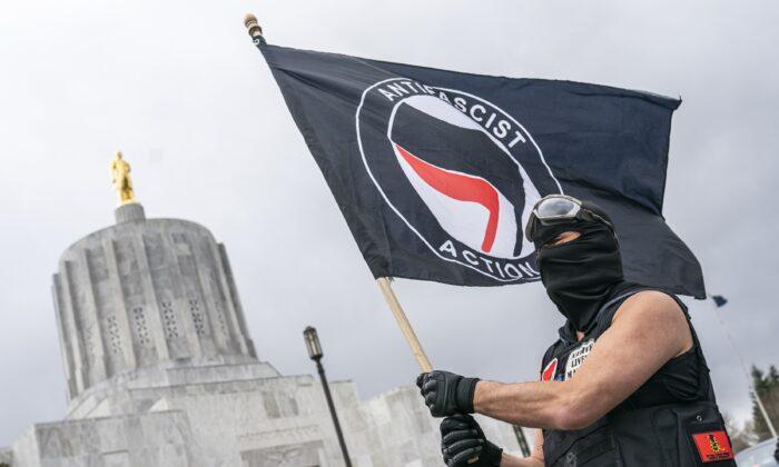Un hombre ondea una bandera Antifa en el Capitolio de Oregón en Salem (Oregón) el 28 de marzo de 2021. (Nathan Howard/Getty Images)