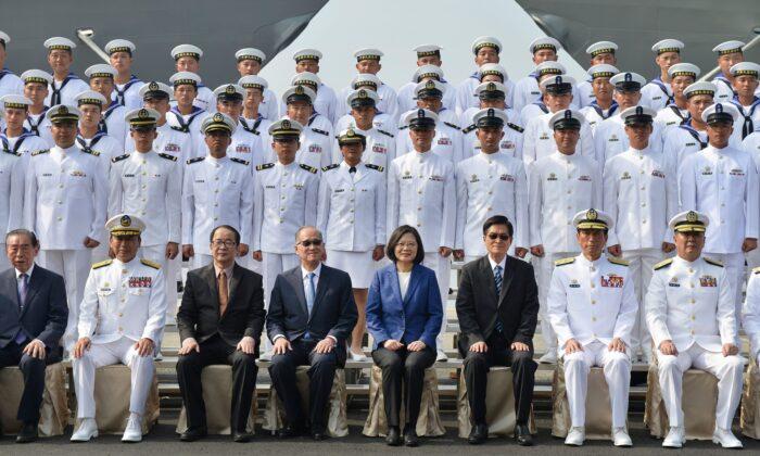 """La presidenta de Taiwán, Tsai Ing-Wen (C, de azul), y el personal naval reunido participan en una ceremonia para poner en servicio dos fragatas de misiles guiados de clase Perry estadounidenses en la Armada de Taiwán, en el puerto sureño de Kaohsiung el 8 de noviembre de 2018. La presidenta Tsai Ing-wen prometió el 8 de noviembre que Taiwán no """"cederá ni un paso"""" en su defensa al inaugurar dos fragatas compradas a Estados Unidos destinadas a potenciar las capacidades navales de la isla frente a las amenazas de China. (Chris Stowers/AFP/Getty Images)"""