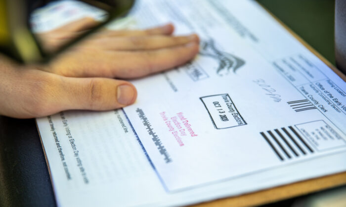 Un trabajador electoral sella la boleta de un votante antes de depositarla en una caja segura, en un lugar de entrega de boletas, en Austin, Texas, el 13 de octubre de 2020. (Sergio Flores/Getty Images)