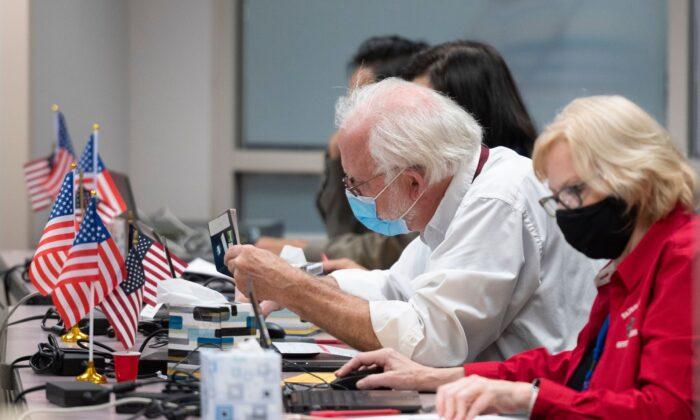 Un hombre verifica la identificación de un votante antes de entregarle una boleta en un lugar de votación anticipada, en Fairfax, Virginia, el 18 de septiembre de 2020. (ANDREW CABALLERO-REYNOLDS/AFP a través de Getty Images)