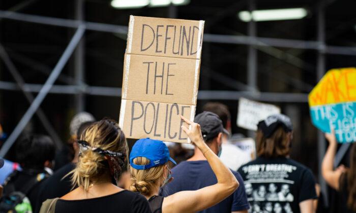 Una manifestante sostiene un letrero que pide 'desfinanciar a la policía' durante una protesta de Black Lives Matter en Manhattan, Nueva York, el 13 de julio de 2020. (Chung I Ho/The Epoch Times)
