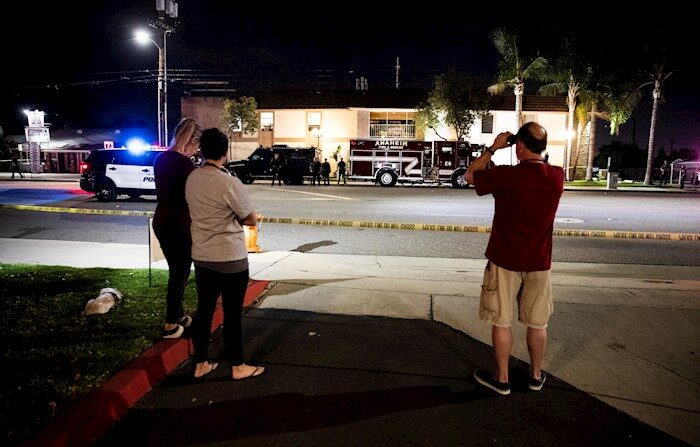 Varias personas observan tras el cordón policial luego de que al menos cuatro personas, incluido un menor de edad, murieran este miércoles en un nuevo tiroteo ocurrido en Estados Unidos, esta vez en un edificio de oficinas en la ciudad de Orange, al sur de Los Ángeles. (EFE/EPA/ETIENNE LAURENT)