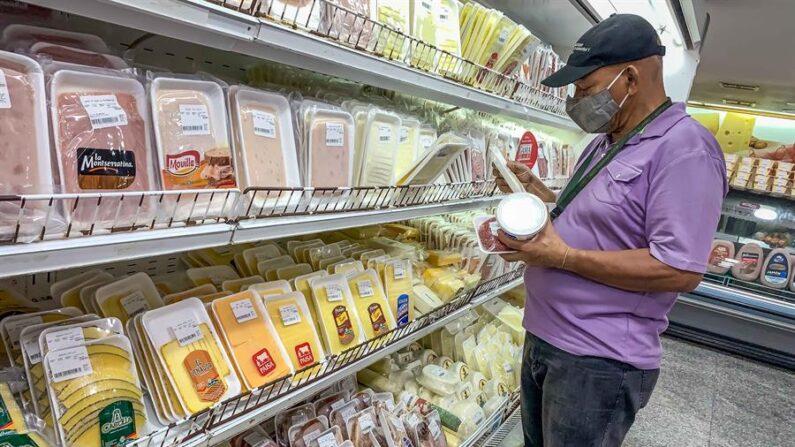 Un hombre escoge productos en una nevera de productos de carnes frías en un supermercado en Caracas (Venezuela). EFE/Miguel Gutiérrez/Archivo