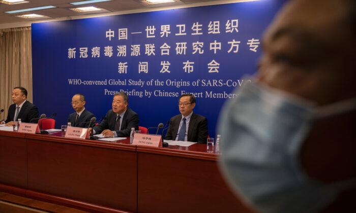 El jefe del Grupo de Expertos para la Respuesta al COVID, en la Comisión Nacional de Salud de China, Liang Wannian, en el centro, responde una pregunta mientras se sienta con sus colegas Feng Zijian, a la derecha, Tong Yigan, segundo a la izquierda, en una conferencia de prensa sobre el informe de la Organización Mundial de la Salud (OMS) que buscaba los orígenes del SARS-CoV-2, en el Comité Nacional de Salud, el 31 de marzo de 2021, en Beijing, China. (Kevin Frayer/Getty Images)