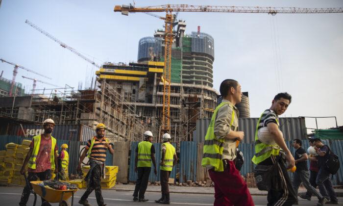 Los trabajadores de la construcción chinos se dirigen a casa luego de trabajar en la obra de un nuevo centro comercial llamado The Mall at One Galle Face, que es parte del complejo de oficinas y ventas comerciales Shangri-La administrado por China en Colombo, Sri Lanka, el 10 de noviembre de 2018. (Paula Bronstein/Getty Images)
