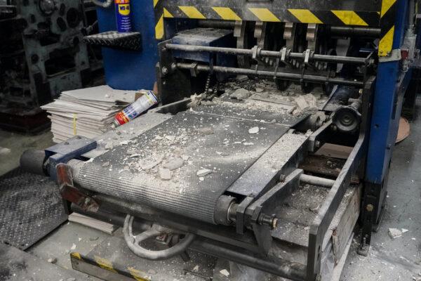 Escombros de construcción sobre el equipo de una imprenta que imprime la edición de Hong Kong de The Epoch Times el 12 de abril de 2021. (Adrian Yu/The Epoch Times)