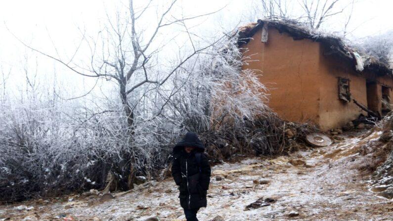 """Wang Fuman, también conocido como el """"niño congelado"""", camina por la carretera en Ludian, en la provincia suroccidental china de Yunnan, el 12 de enero de 2018. (AFP/Getty Images)"""