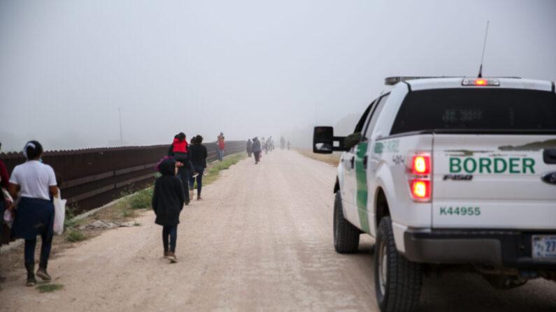 Un grupo de inmigrantes ilegales con la Patrulla Fronteriza después de cruzar la frontera entre Estados Unidos y México en La Joya, Texas, el 10 de abril de 2021. (Charlotte Cuthbertson/The Epoch Times)