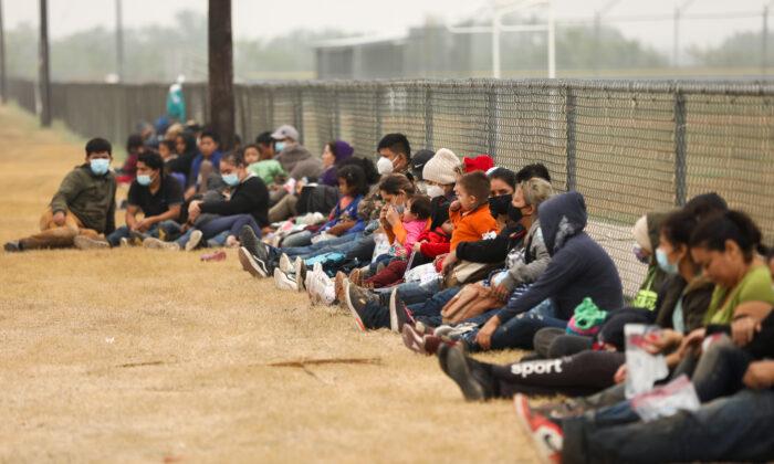 Un grupo de inmigrantes ilegales espera a la Patrulla Fronteriza luego de cruzar la frontera entre Estados Unidos y México en La Joya, Texas, el 10 de abril de 2021. (Charlotte Cuthbertson/The Epoch Times)