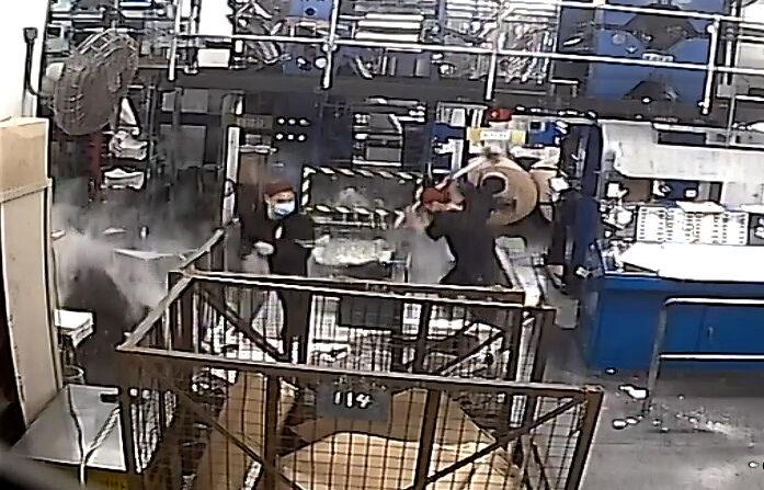 Una captura de pantalla de CCTV que muestra a intrusos vestidos de negro, uno de ellos blandiendo un mazo, dañando el equipo de la imprenta de la edición de Hong Kong de The Epoch Times el 12 de abril de 2021.(Epoch Times)