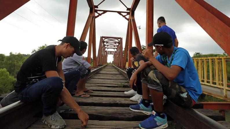 Migrantes hondureños conversan en una vía férrea de la población de Huixtla (México) donde permanecen en su travesía hacia Estados Unidos. EFE/José Méndez/Archivo